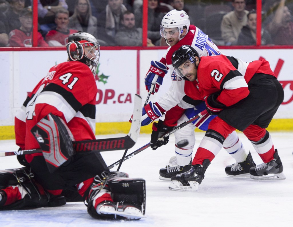 Montreal Canadiens left wing Kenny Agostino (47) and Ottawa Senators defenseman Dylan DeMelo (2) fight for the puck during second-period NHL hockey ga