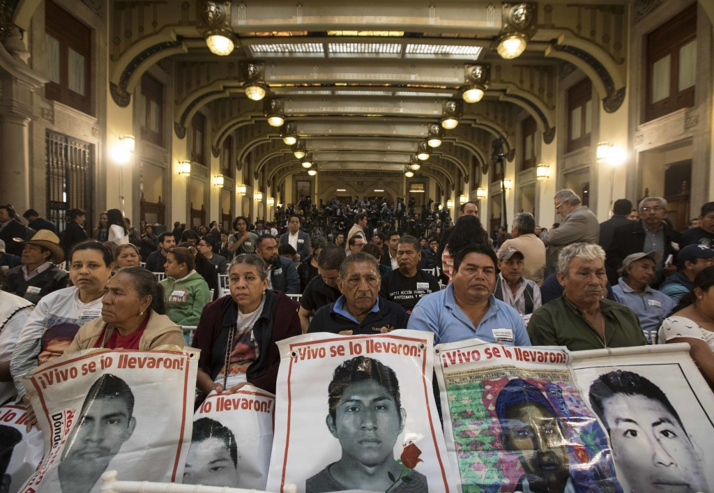 Family members hold posters that show images of their missing sons, during a signing ceremony at the National Palace in Mexico City, on Monday, Dec. 3