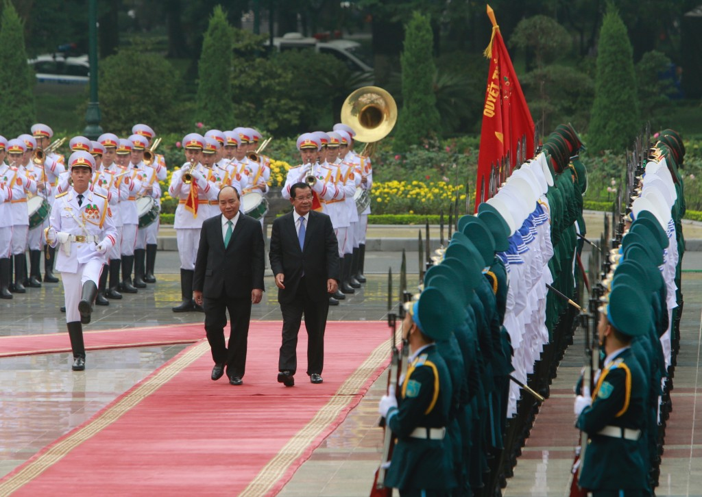 Cambodian Prime Minister Hun Sen, center right, and his Vietnamese counterpart Nguyen Xuan Phuc, center left, review an honor guard in Hanoi, Vietnam