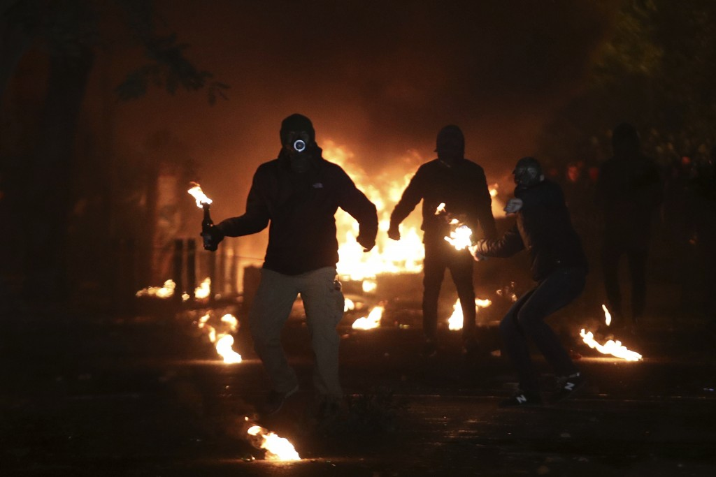 Hooded youths throw petrol bombs at riot police in the Athens neighborhood of Exarchia, a haven for extreme leftists and anarchists, Thursday, Dec. 6,