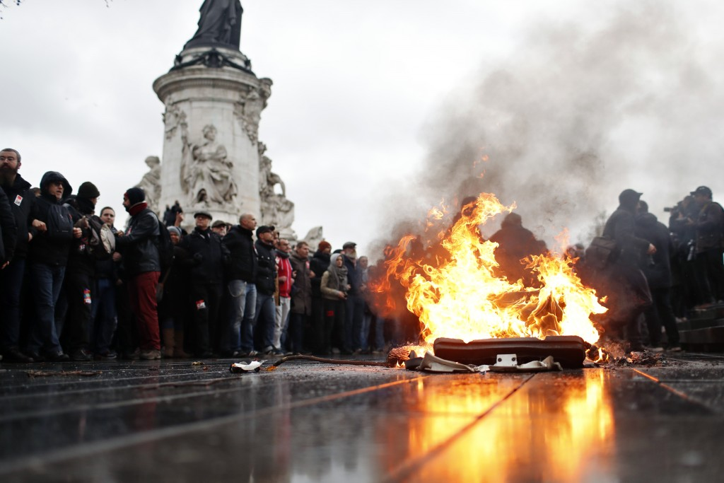 A bin is burning as school children demonstrate in Paris, Friday Dec.7, 2018. Footage showing the brutal arrest of high school students protesting out