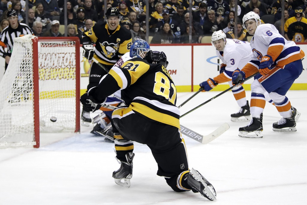 Pittsburgh Penguins' Phil Kessel (81) gets the puck behind New York Islanders goaltender Thomas Greiss for the first of his two goals of the second pe