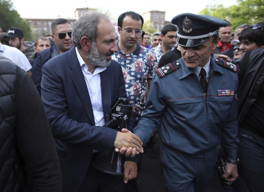 FILE - In this file photo taken on Monday, April 30, 2018, Armenian protest leader Nikol Pashinian, left, shakes hands with a police officer during a