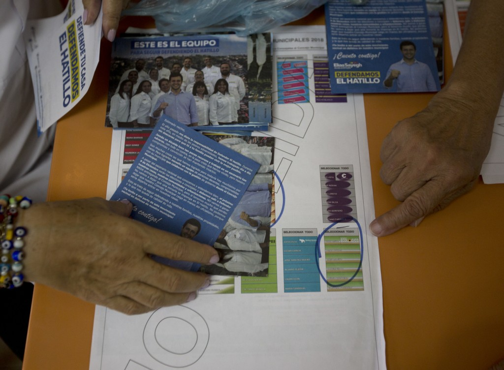 In this Dec. 5, 2018 photo, people are familiarized with the ballot for local elections during a campaign event by Fernando Melena, who is running to