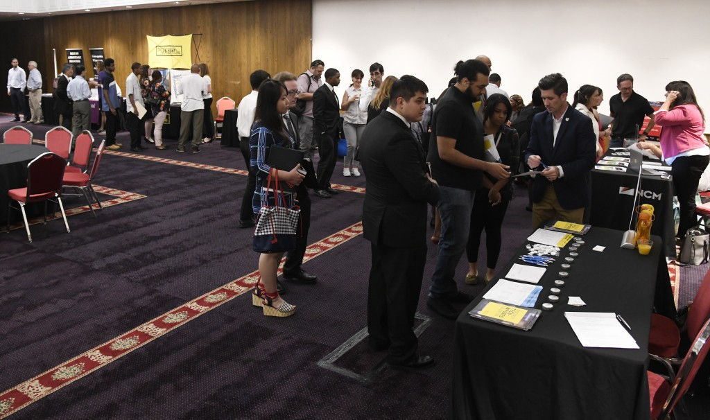 FILE- In this June 20, 2018, file photo people attend a job fair in Chicago. On Friday, Dec. 7, the U.S. government issues the November jobs report. (