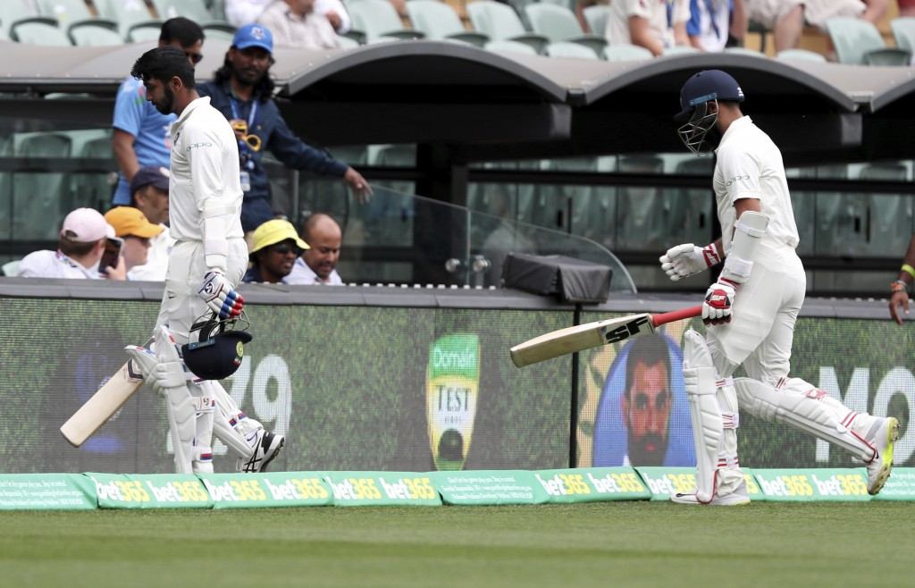 India's Mohammed Shami and Jasprit Bumrah walk from the field after India was dismissed for 250 runs in their first innings during the first cricket t