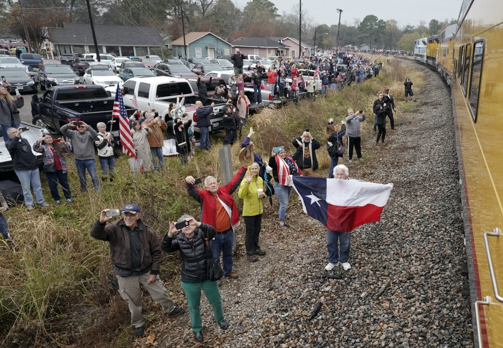 People pay their respects as the train carrying the casket of former President George H.W. Bush passes Thursday, Dec. 6, 2018, along the route from Sp