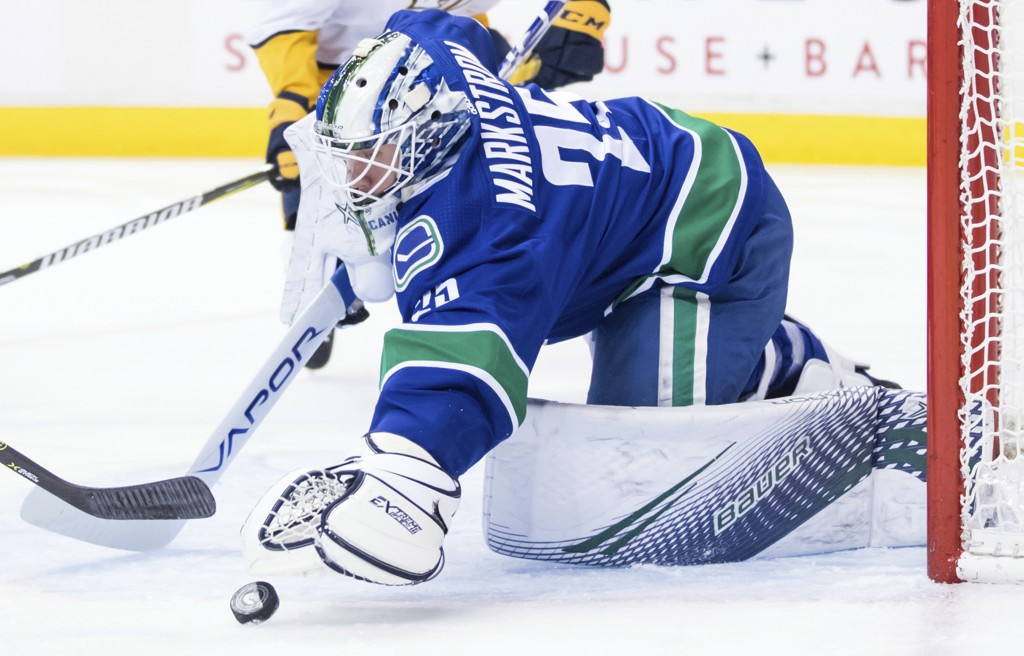 Vancouver Canucks goalie Jacob Markstrom, of Sweden, covers up the puck during the first period of an NHL hockey game against the Nashville Predators