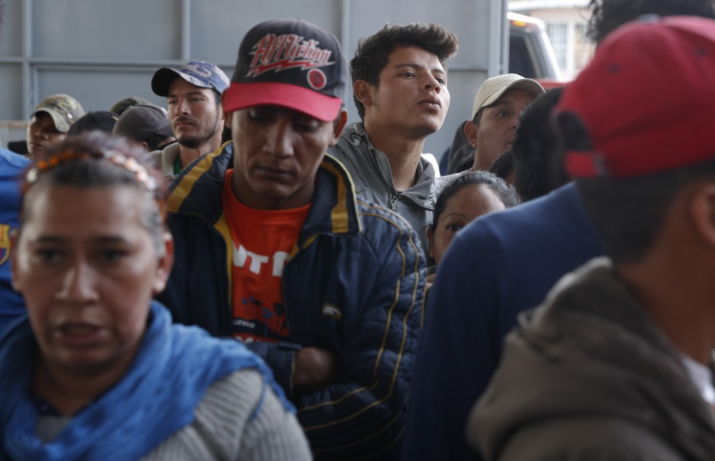 In this Dec. 4, 2018 photo, Central American migrants wait in line at a job fair where they are able to apply for Mexican work permits, recover lost H