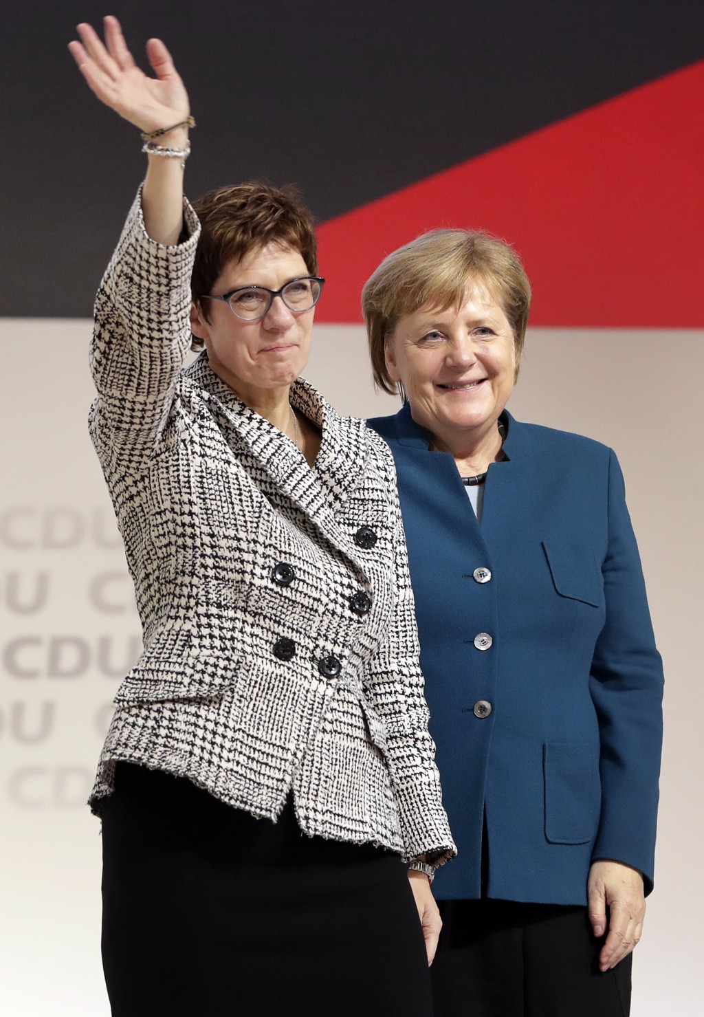 Newly elected CDU chairwoman Annegret Kramp-Karrenbauer, left, is flanked by German Chancellor Angela Merkel, right, as she waves during the party con