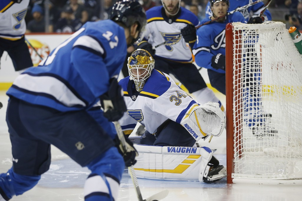 St. Louis Blues goaltender Jake Allen (34) watches Winnipeg Jets' Adam Lowry (17), who looks for an opening during the second period of an NHL hockey