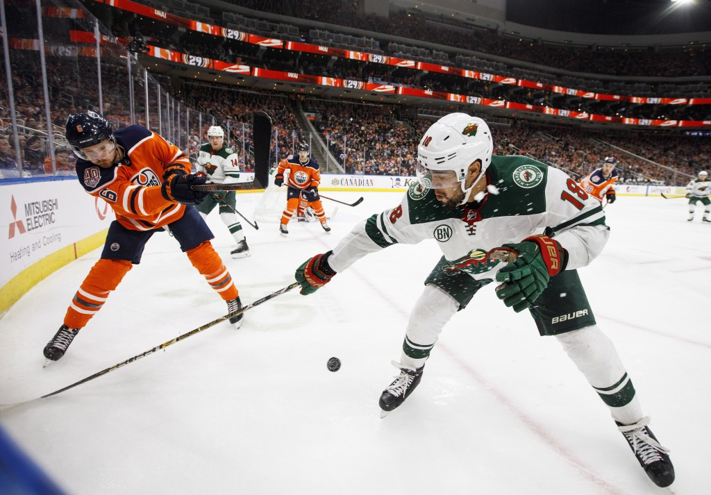 Minnesota Wild left wing Jordan Greenway (18) and Edmonton Oilers defenseman Adam Larsson (6) battle for the puck during the third period of an NHL ho