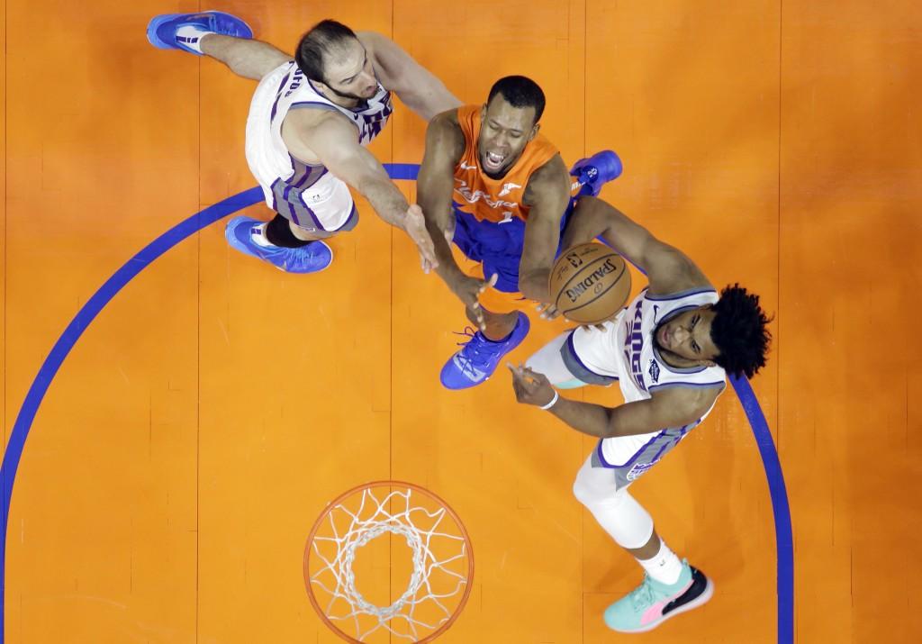 Cleveland Cavaliers' Rodney Hood, center, drives to the basket between Sacramento Kings' Kosta Koufos, left, and Sacramento Kings' Marvin Bagley III i