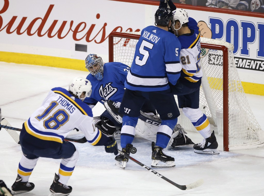 Winnipeg Jets goaltender Connor Hellebuyck (37) keeps his eye on the pass to St. Louis Blues' Robert Thomas (18) as Jets' Dmitry Kulikov (5) defends a