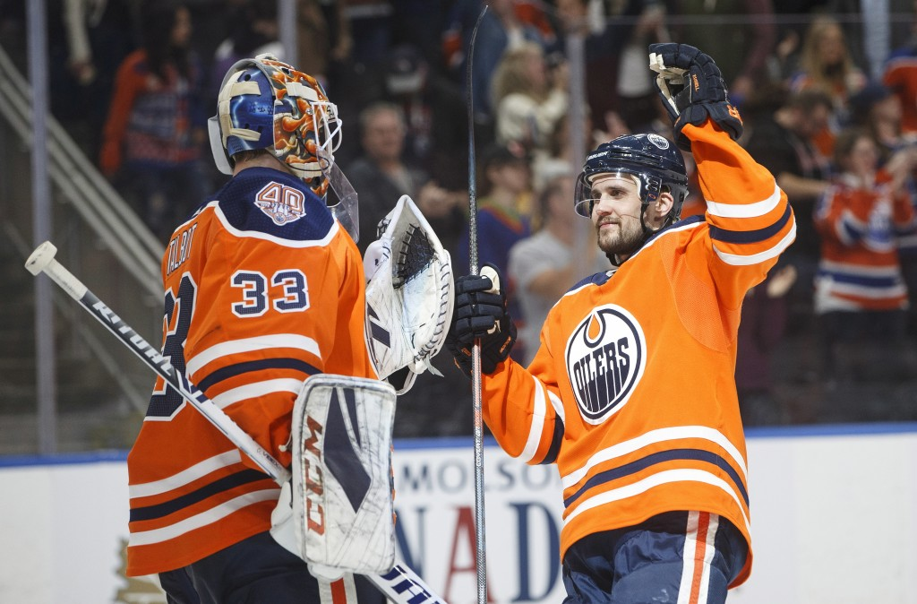 Edmonton Oilers goaltender Cam Talbot (33) and teammate Kris Russell (4) celebrate the team's win over the Minnesota Wild in an NHL hockey game in Edm