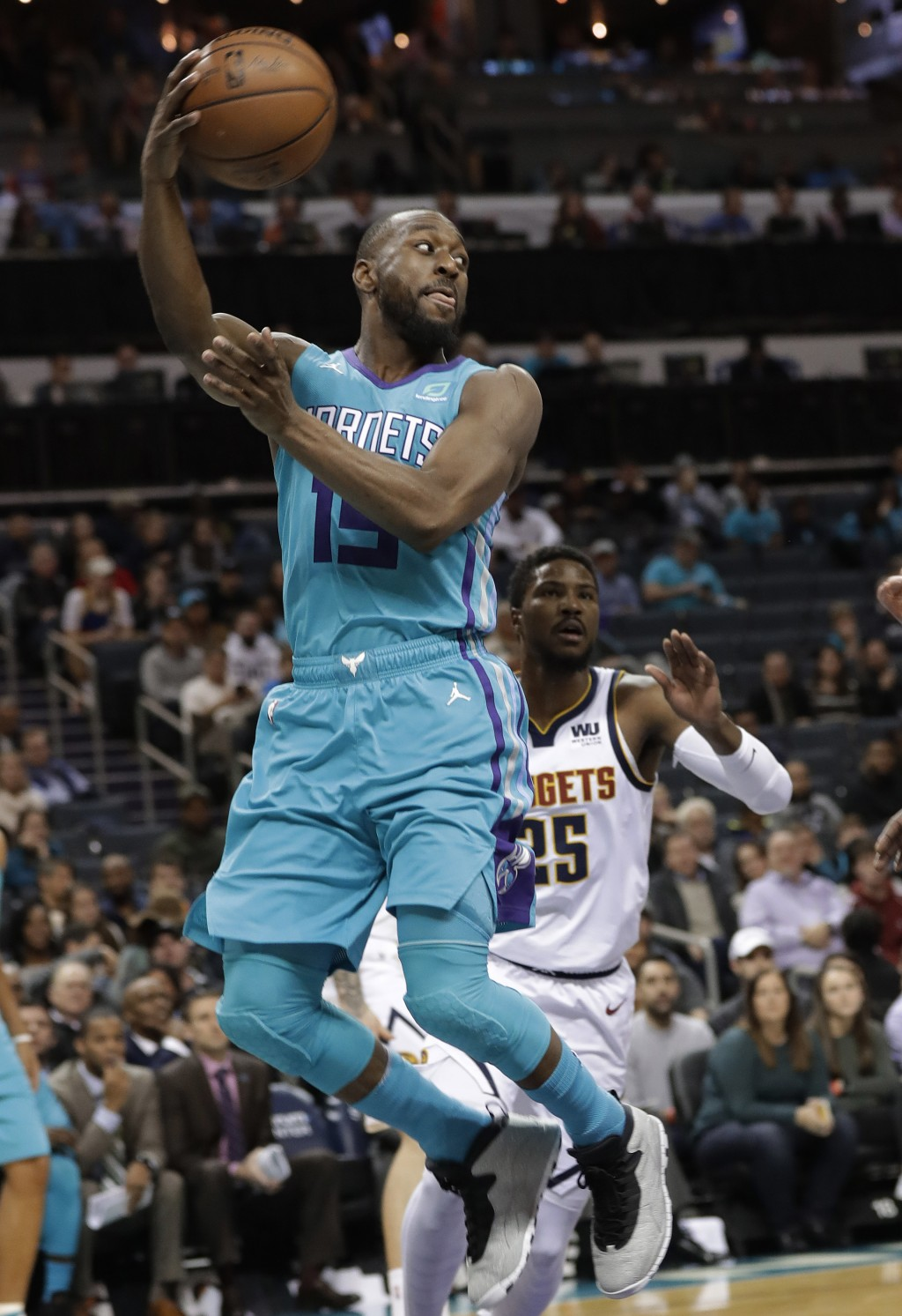 Charlotte Hornets' Kemba Walker (15) looks to pass the ball as Denver Nuggets' Malik Beasley (25) watches during the first half of an NBA basketball g