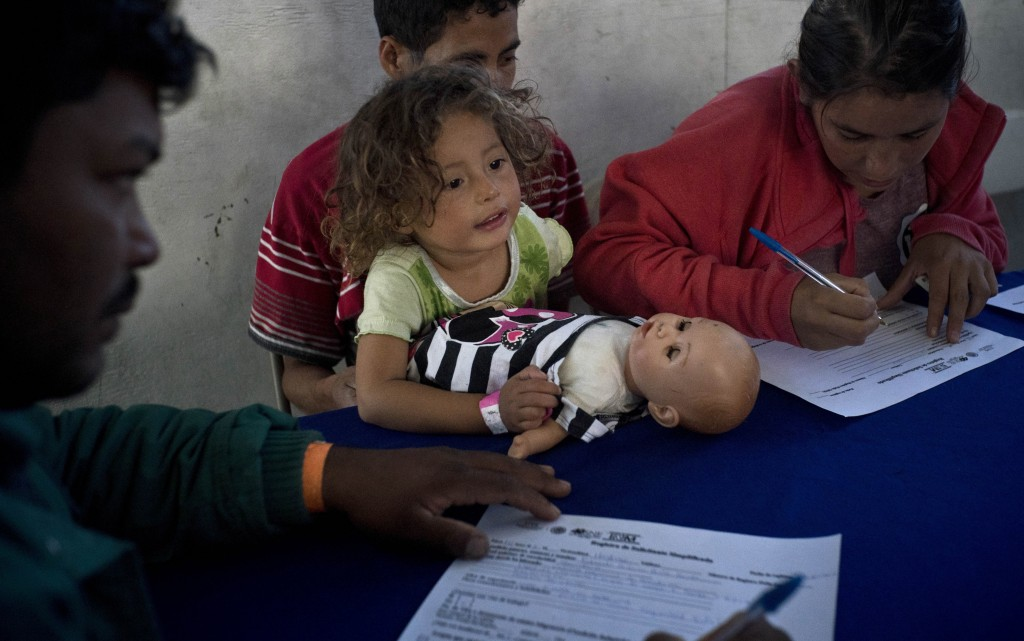 In this Nov. 27, 2018 photo, a child holds her doll as her guardians apply for jobs at a job fair for recently arrived migrants in Tijuana, Mexico. Pr