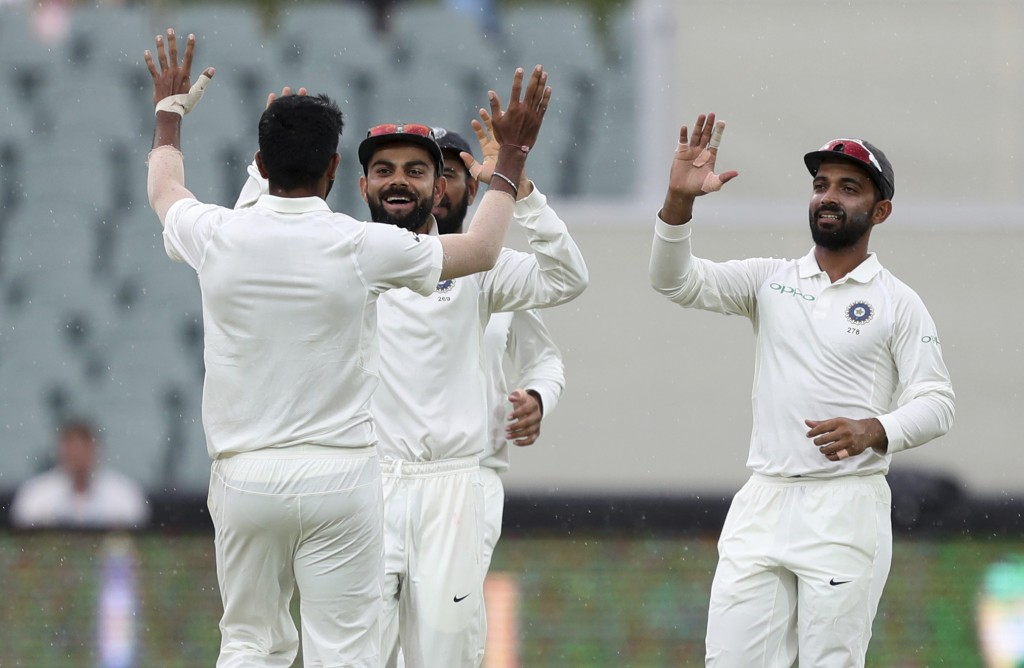 India's Virat Kohli, second left, congratulates teammate Jasprit Bumrah, left, after taking the wicket of Australia's Mitchell Starc during the first
