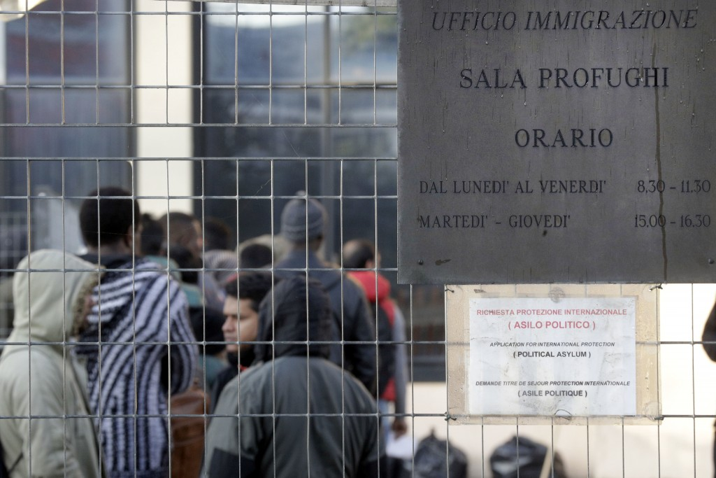 In this photo taken on Friday, Dec. 7, 2018, people queue at the political asylum migration office at the Italian police headquarters, in Rome. Thousa