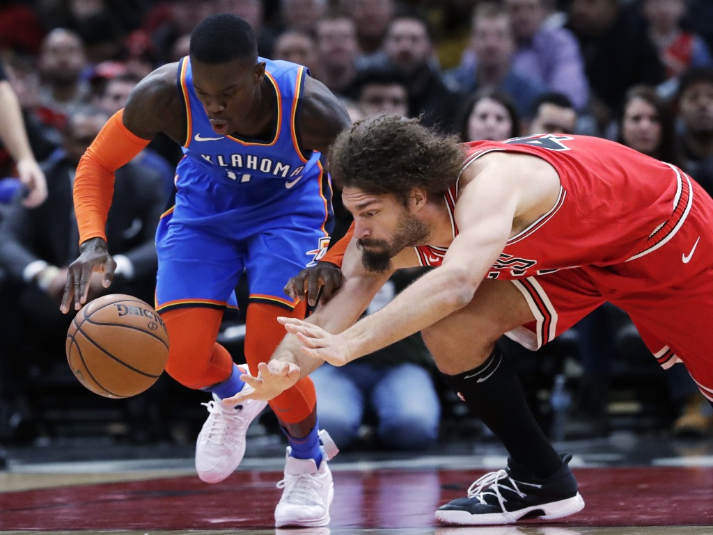 Oklahoma City Thunder guard Dennis Schroeder, left, and Chicago Bulls center Robin Lopez vie for a loose ball during the first half of an NBA basketba