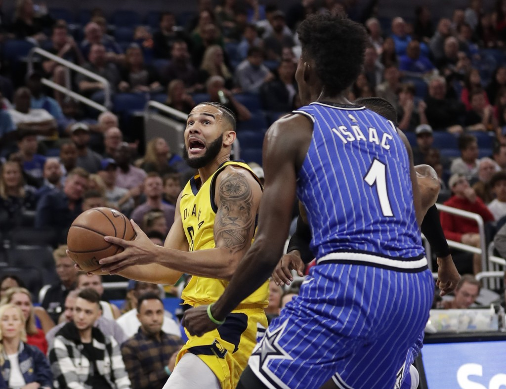 Indiana Pacers' Cory Joseph, left, looks for a shot as Orlando Magic's Jonathan Isaac (1) defends during the first half of an NBA basketball game Frid...