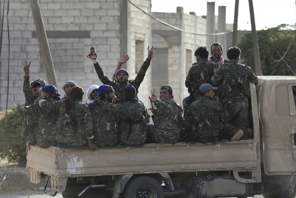 FILE - In this July 22, 2017 file photo, Arab and Kurdish fighters with the U.S.-backed Syrian Democratic Forces (SDF), move to the front line to batt