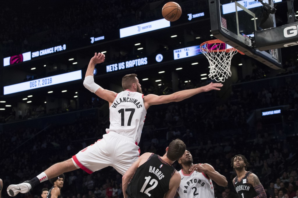 Brooklyn Nets forward Joe Harris (12) fouls Toronto Raptors center Jonas Valanciunas (17) during the first half of an NBA basketball game, Friday, Dec