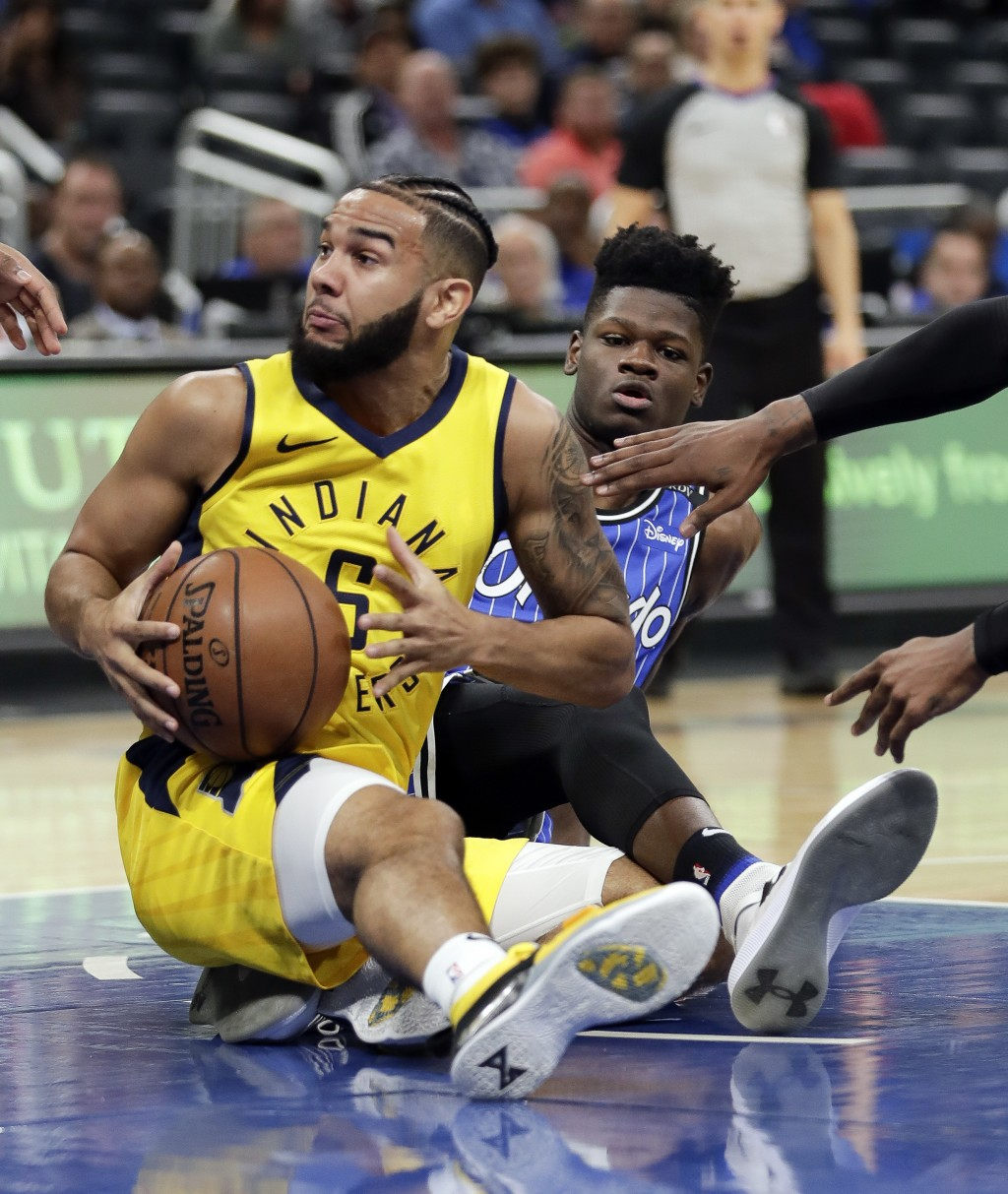 Indiana Pacers' Cory Joseph, left, looks to pass the ball after getting tangled up with Orlando Magic's Mo Bamba during the first half of an NBA baske...