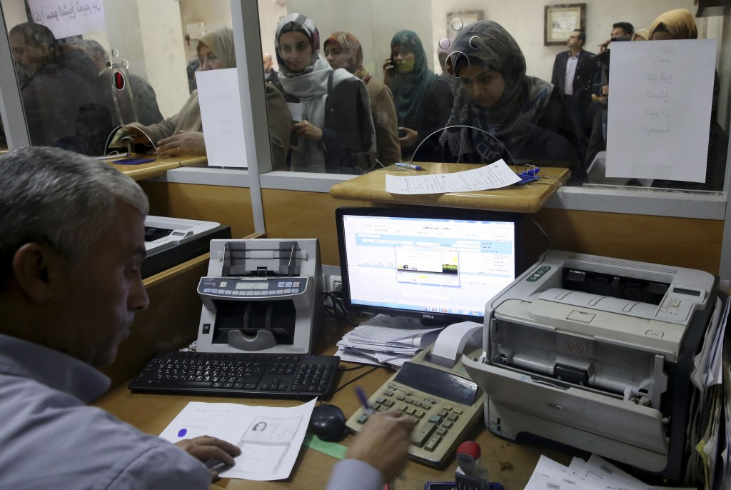 Palestinian Hamas government employees queue to receive 50 percent of their long-overdue salaries donated by Qatar, at the main Gaza Post Office, in G
