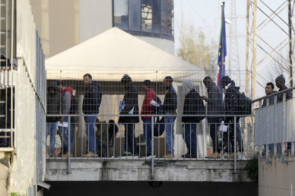 In this photo taken on  Friday, Dec. 7, 2018, people queue at the political asylum migration office at the Italian police headquarters, in Rome. Thous