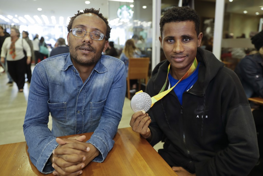 In this Nov. 20, 2018 photo, Ethiopian paralympic athletes Megersa Bati, left, and Tamiru Kefeyalew Demisse, holding the silver medal he won in the 1,