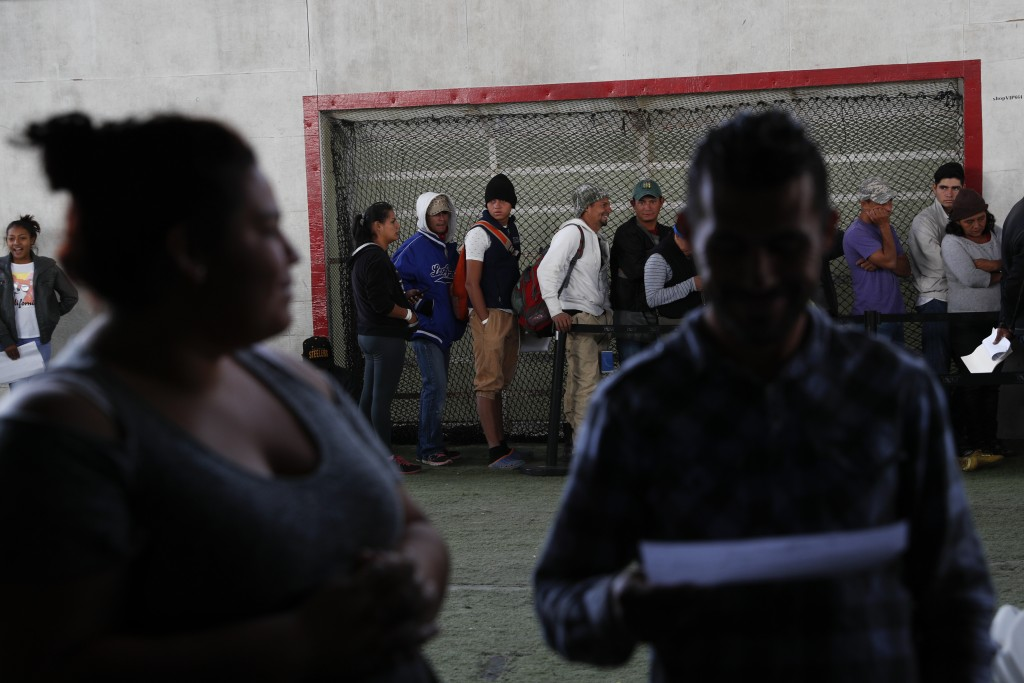In this Dec. 4, 2018 photo, Central American migrants wait in lines at a job fair, where they are able to apply for Mexican work permits, recover lost