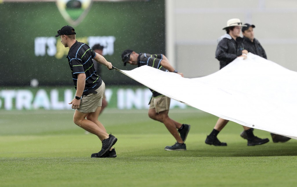 Ground staff bring covers onto the field as rain stops play during the first cricket test between Australia and India in Adelaide, Australia,Saturday,
