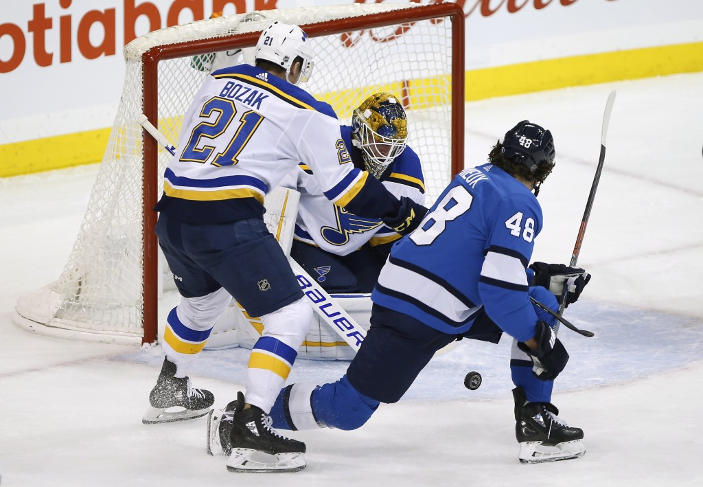 St. Louis Blues goaltender Jake Allen (34) makes the save on a shot by Winnipeg Jets' Brendan Lemieux (48) as Blues' Tyler Bozak (21) defends during t