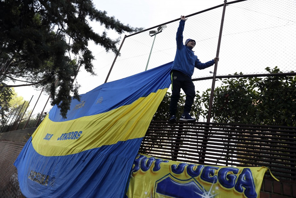 A Boca Juniors supporter climbs on a fence during a gathering of fans outside the team hotel in Madrid Saturday, Dec. 8, 2018. The Copa Libertadores F