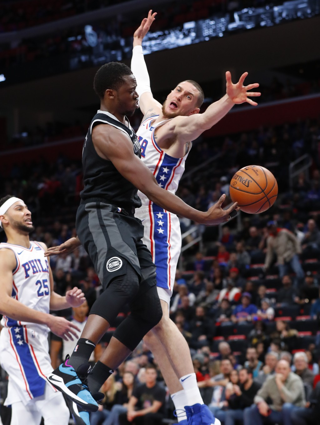 Detroit Pistons guard Reggie Jackson (1) passes around Philadelphia 76ers forward Mike Muscala (31) in the first half of an NBA basketball game in Det