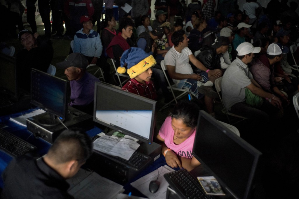 In this Nov. 27, 2018 photo, migrants who travel in a caravan attend a job fair to find work in Tijuana, Mexico. The previous week the job fair was on