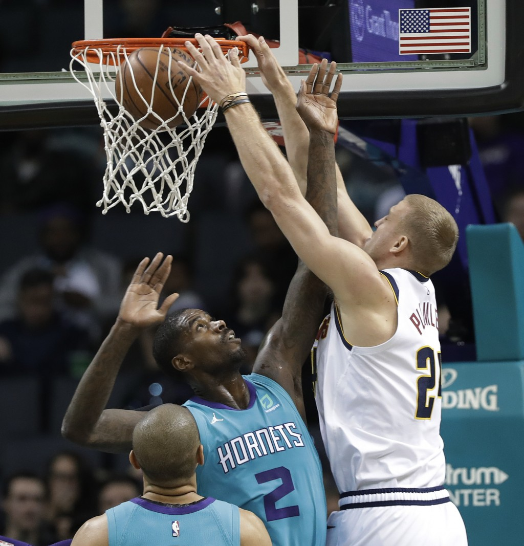 Denver Nuggets' Mason Plumlee (24) dunks against Charlotte Hornets' Marvin Williams (2) during the first half of an NBA basketball game in Charlotte,