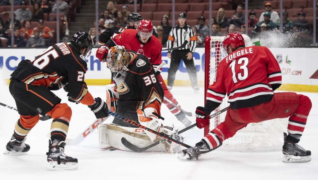 Anaheim Ducks goaltender John Gibson, center, blocks the shot by Carolina Hurricanes left wing Warren Foegele, right, during the first period of an NH