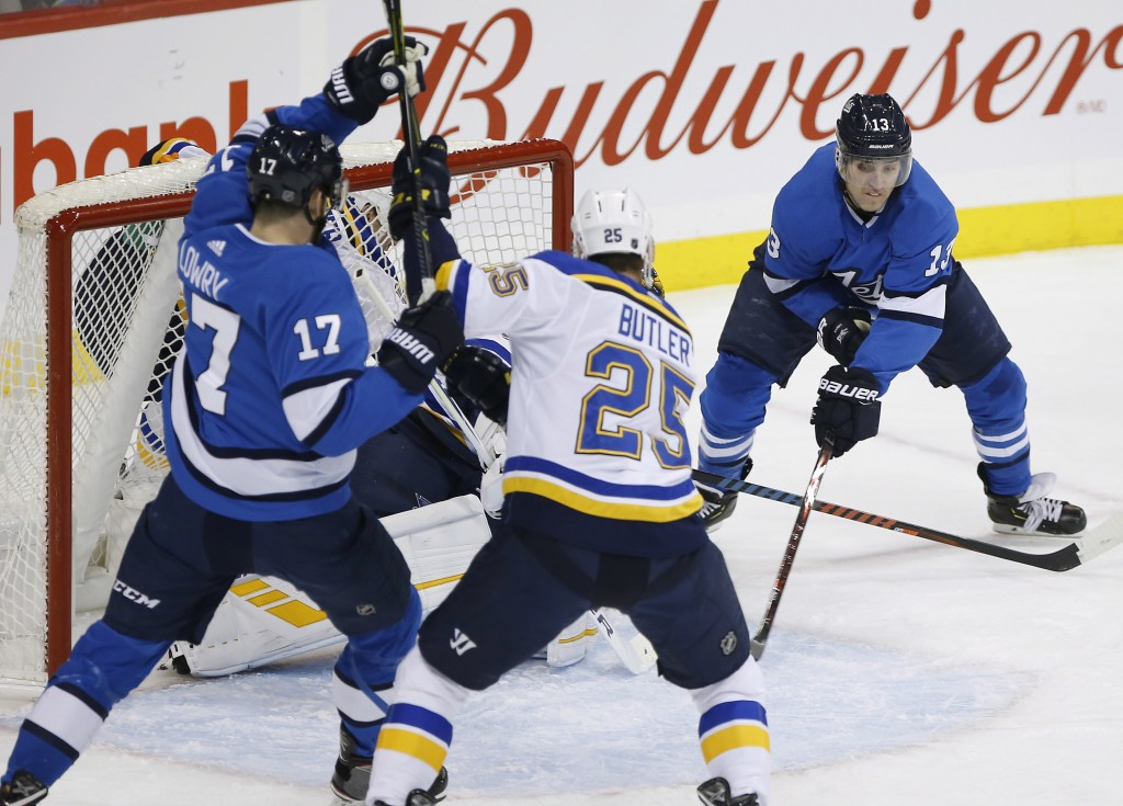 Winnipeg Jets' Brandon Tanev (13) attempts the wraparound on St. Louis Blues goaltender Jake Allen (34) as Blues' Chris Butler (25) defends against Je