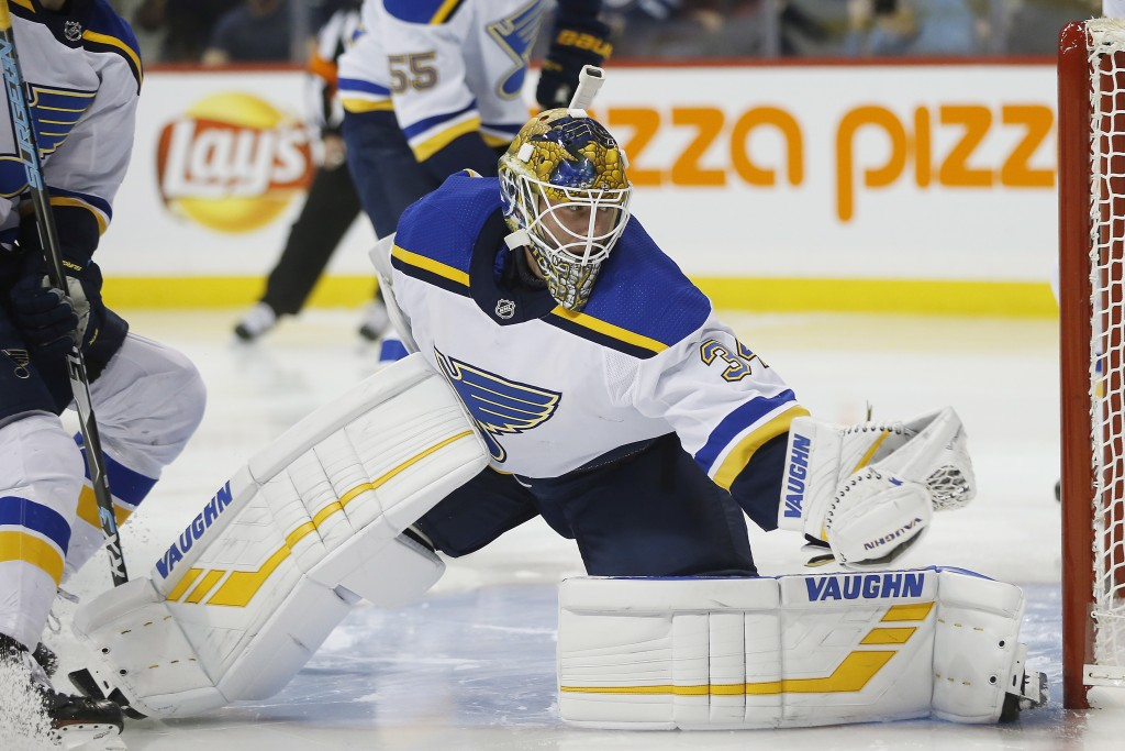 St. Louis Blues goaltender Jake Allen gloves the puck on a shot from Winnipeg Jets' Adam Lowry during the second period of an NHL hockey game Friday,