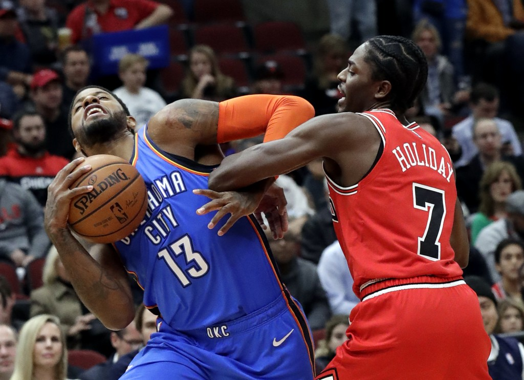 Oklahoma City Thunder forward Paul George, left, controls the ball against Chicago Bulls guard Justin Holiday during the first half of an NBA basketba