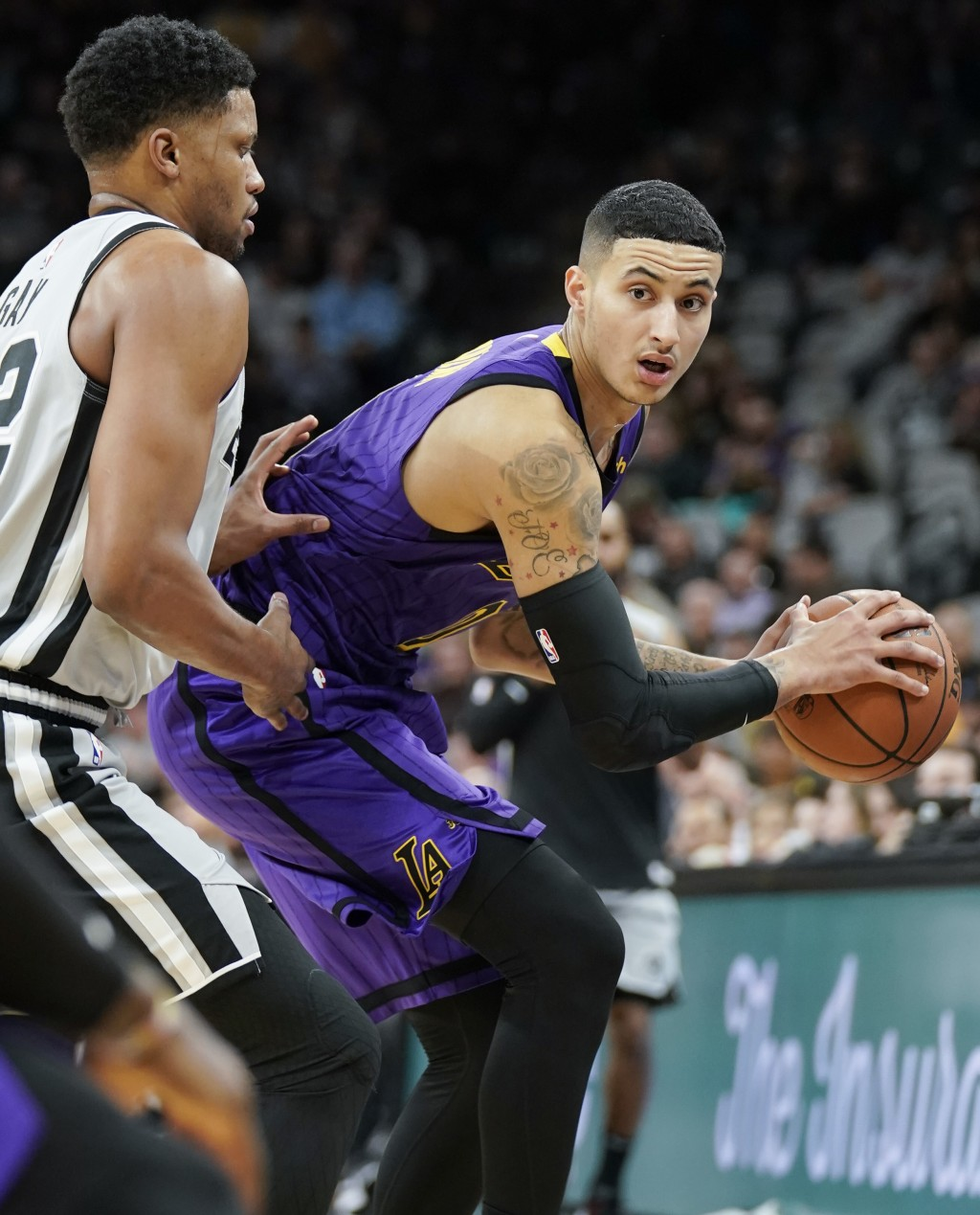 Los Angeles Lakers' Kyle Kuzma, right, looks to pass the ball as San Antonio Spurs' Rudy Gay defends during the first half of an NBA basketball game F