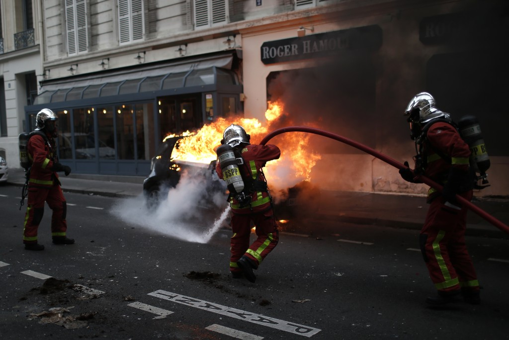 Firefighters put off a fire after clashes Saturday, Dec. 8, 2018 in Paris. French riot police fired tear gas and water cannon in Paris on Saturday, tr