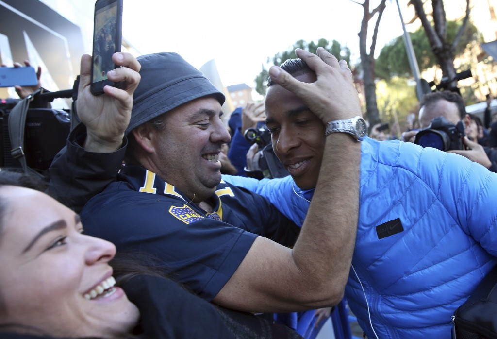 Boca Juniors' Sebastian Villa, right, is hugged by a supporter as the team arrives at their hotel in Madrid Saturday, Dec. 8, 2018. The Copa Libertado