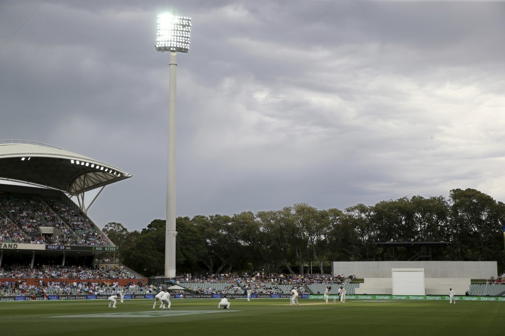 Play continues under lights following rain delays during the first cricket test between Australia and India in Adelaide, Australia,Saturday, Dec. 8, 2