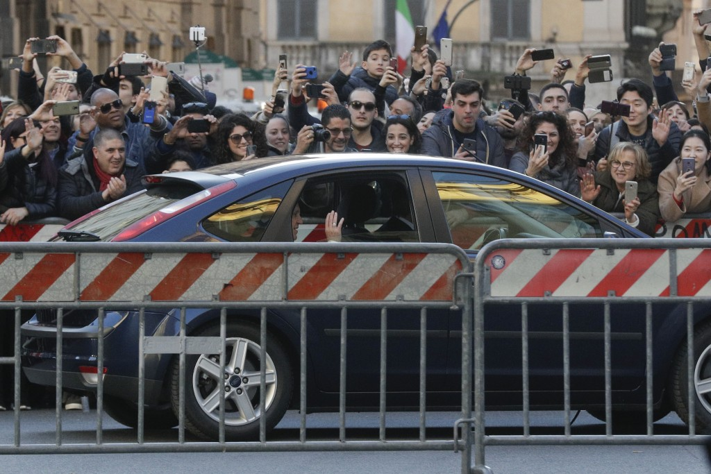 Pope Francis waves to faithful as he arrives on a car to pray in front of the Virgin Mary statue on the occasion of the immaculate conception feast at