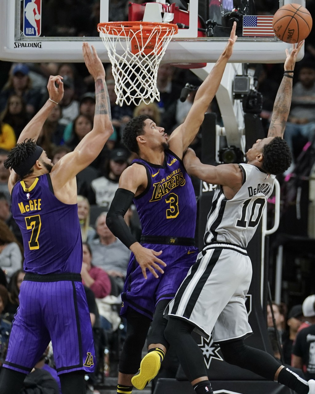 San Antonio Spurs' DeMar DeRozan (10) shoots against Los Angeles Lakers' Josh Hart (3) and JaVale McGee during the first half of an NBA basketball gam