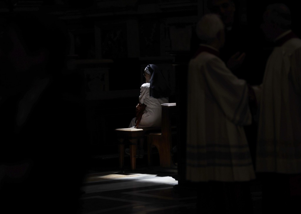 FILE - In this Tuesday, June 26, 2018 file photo, a ray of sun sheds light on nun sitting inside the Basilica of St. John Lateran in Rome. The Vatican