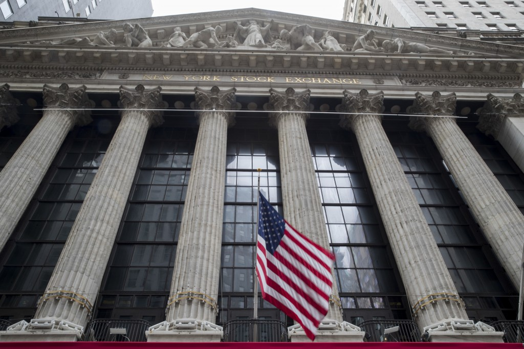 FILE- In this Nov. 20, 2018, file photo an American flag flies outside New York Stock Exchange. The stock market hasn't been this dizzying in years, a...